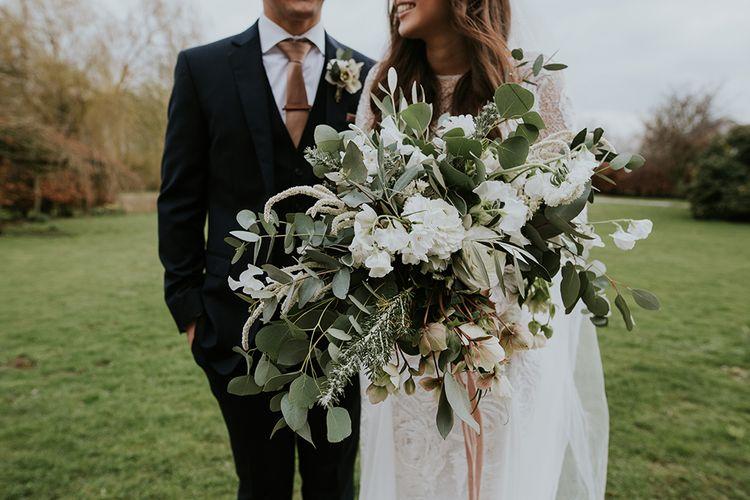 Boho Bride Holding an Oversized White Flower and Foliage Wedding Bouquet