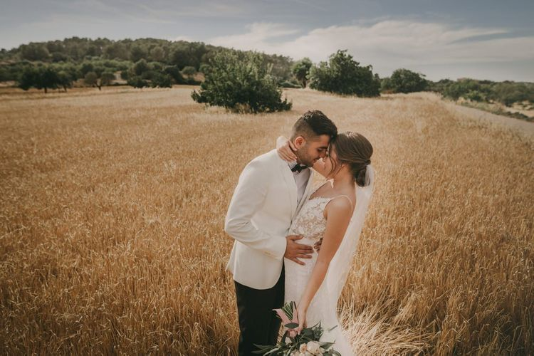 Bride and groom at Mallorca wedding with white tuxedo jacket