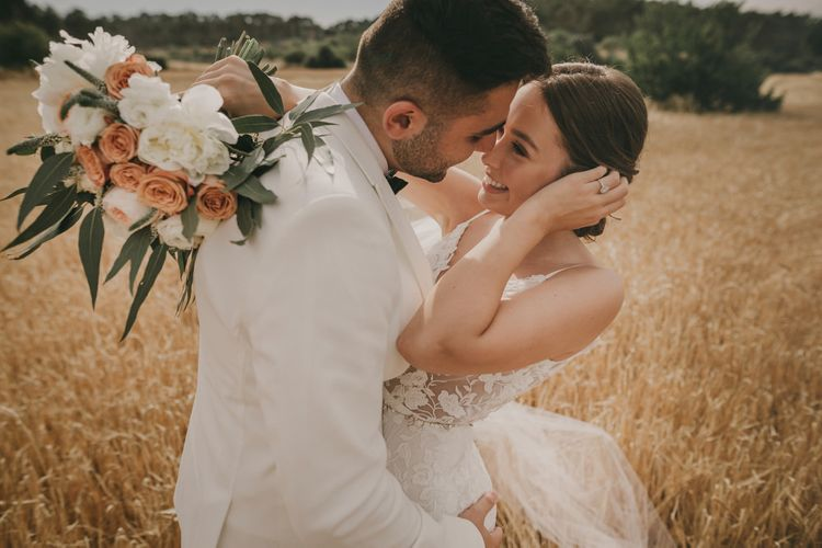 Bride and groom at Mallorca wedding with white tuxedo jacket  and Emmy Mae bride dress