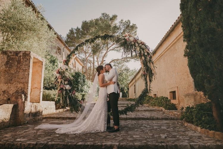 Bride and Groom in white tuxedo jacket with stunning floral moon gate