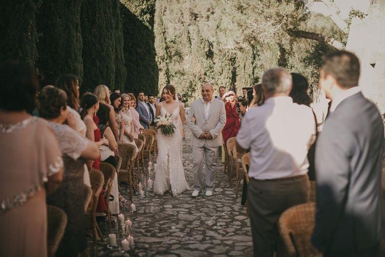 Bride walks down aisle at outdoor ceremony
