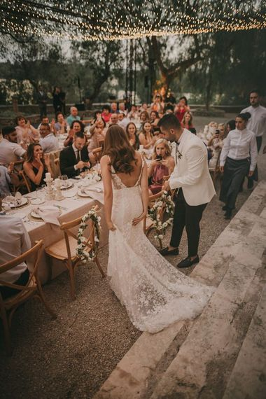 Outdoor wedding reception with fairy light canopy and white tuxedo jacket for groom