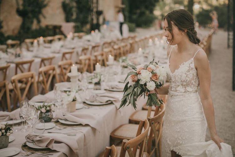 Bride looks at outdoor wedding table set up