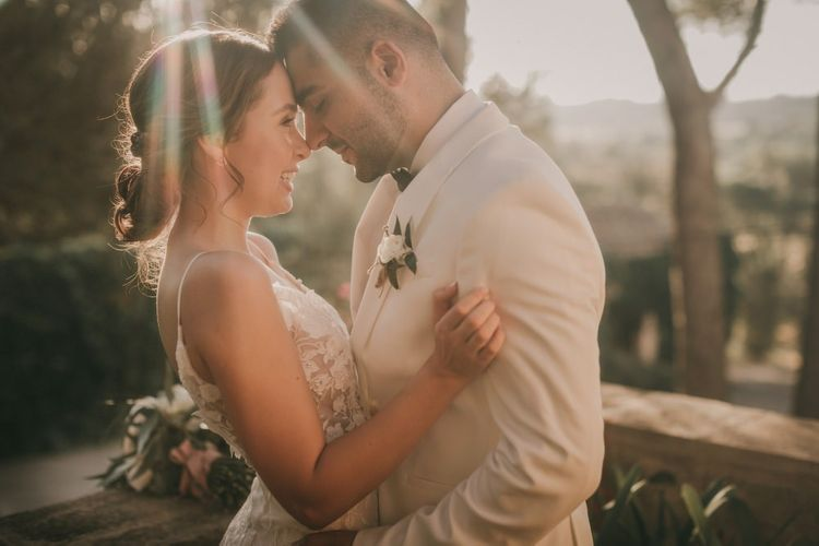 Bride and groom at destination wedding with white tuxedo jacket and lace bride dress