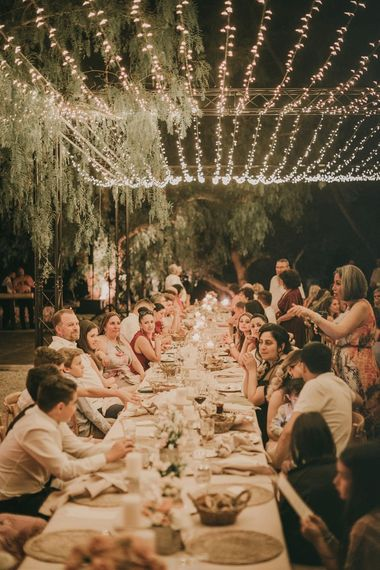 Guests eat under fairy light canopy