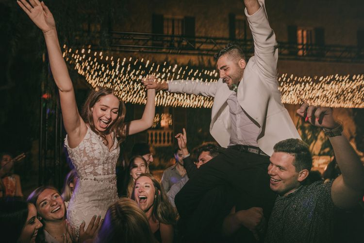 Bride and groom in white tuxedo jacket dance under fairy light canopy