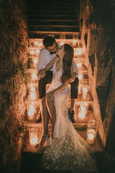 Bride and groom in white tuxedo jacket surrounded by candles
