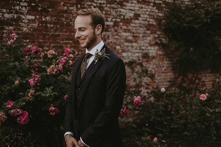 Groom in Black Three-Piece Suit with Patterned Tie