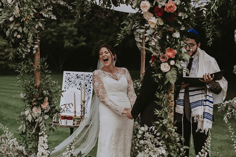 Bride and Groom Underneath Floral Chuppa During Jewish Wedding Ceremony