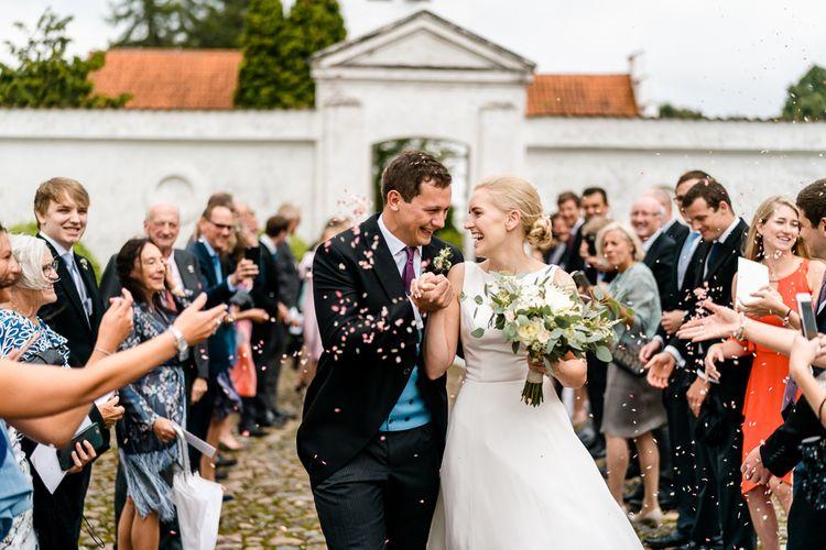 Confetti Exit | Bride in Caroline Castigliano Wedding Dress | Groom in Henry Herbert Tailors Morning Suit | Traditional Green/Blue Danish Wedding at Scandinavian Country House, Jomfruens Egede in Faxe, Denmark | John Barwood Photography