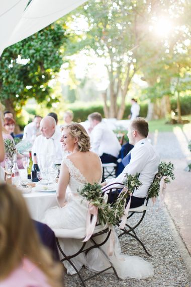 Greenery Garland Chair Back Decor | Bride in Lace Stella York Wedding Dress | Groom in Three Piece Navy Suit | Four Day Italian Destination Wedding at Frattoria Mansi Bernadini Planned by Weddings by Emily Charlotte | Cecelina Photography