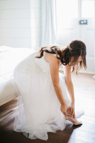 Bride on her wedding morning putting on her pink bridal shoes