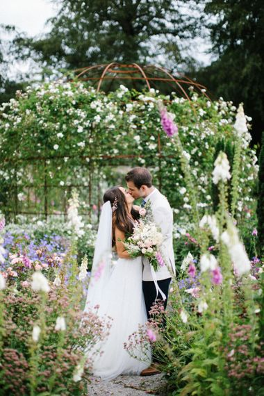 Bride and Groom Kissing in the Gardens Surrounded by Flowers