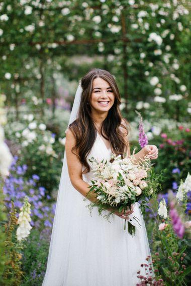 Bride in Catherine Deane Wedding Dress Holding Her Pastel Flower Wedding Bouquet