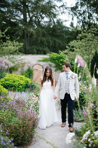 Bride in Catherine Deane Wedding Dress and Groom in Beige Blazer Holding Hands in Middle Lodge Estate's Gardens
