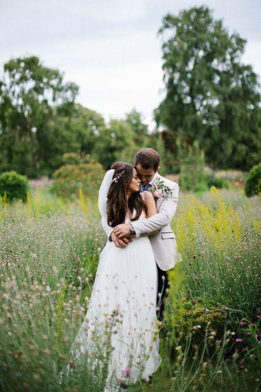 Groom in Beige Jacket Embracing His Bride in a Catherine Deane Wedding Dress