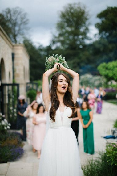 Bride in Catherine Deane Wedding Dress about to toss the bridal bouquet