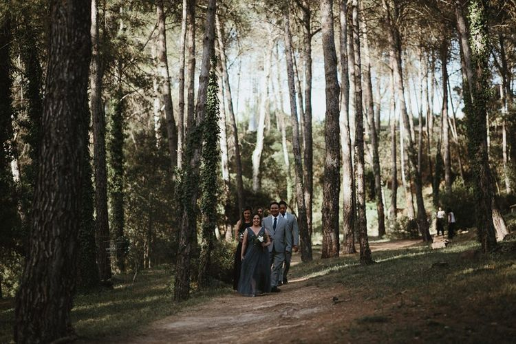 Bridesmaids and groomsmen enter forest ceremony