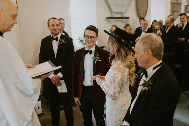 Groom in Red Velvet Jacket with Bow Tie and Glasses Smiling at His Bride During the Wedding Ceremony