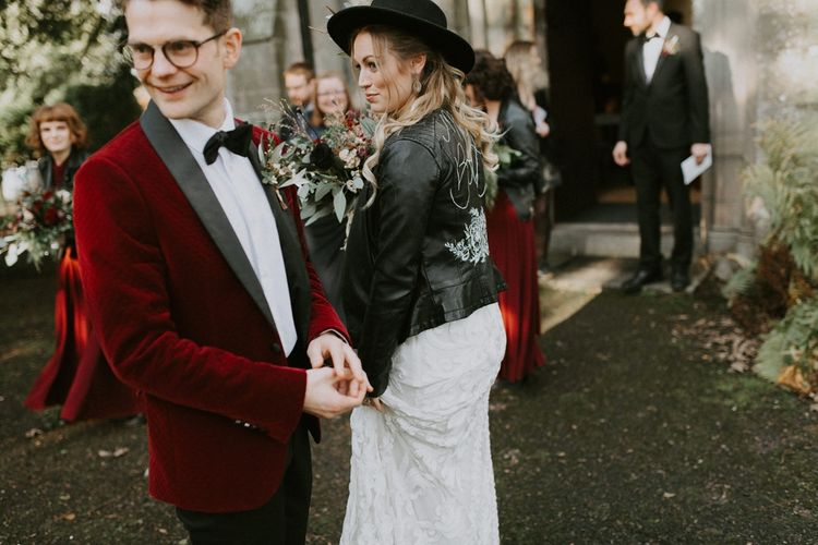 Bride in Fedora Hat and Personalised Leather Jacket  and Groom in Red Velvet Jacket Outside the Church