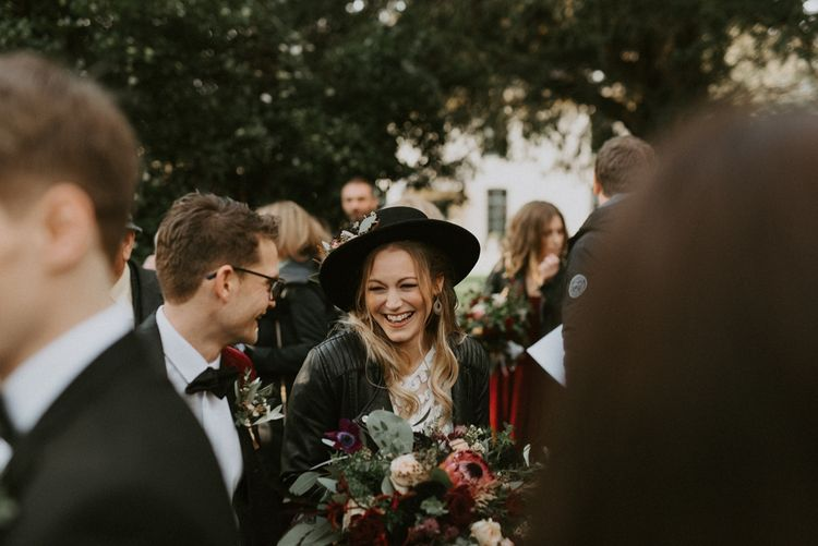 Bride in Fedora Hat and Leather Jacket Laughing Outside the Church