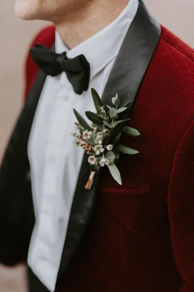 Groom in Red Velvet Tuxedo Jacket with White and Green Buttonhole
