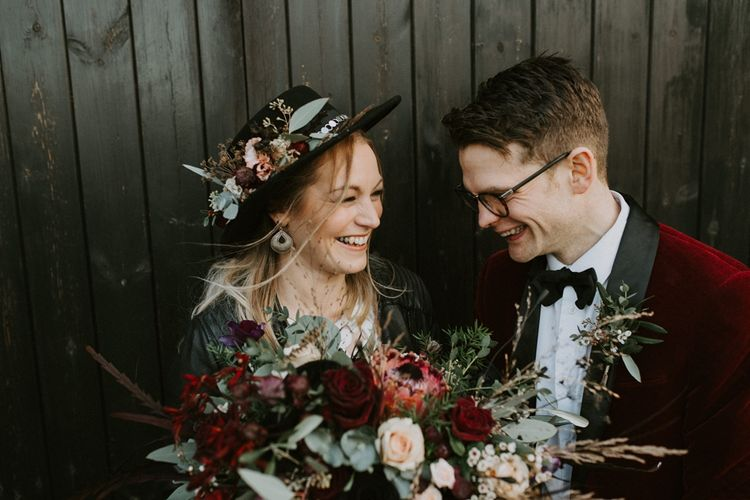 Bride in Floral Fedora Hat and Leather Jacket with Groom in Red Velvet Jacket