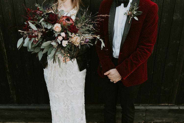 Bride in Phase Eight Wedding Dress Holding an Oversized Bouquet with Red Roses and Proteas and Groom in Red Velvet Tuxedo Jacket