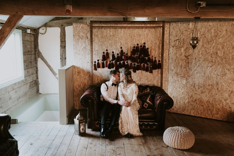 Bride and groom Sitting on a Leather rSofa with Wooden Frame Backdrop Decorated with Hanging Tassels