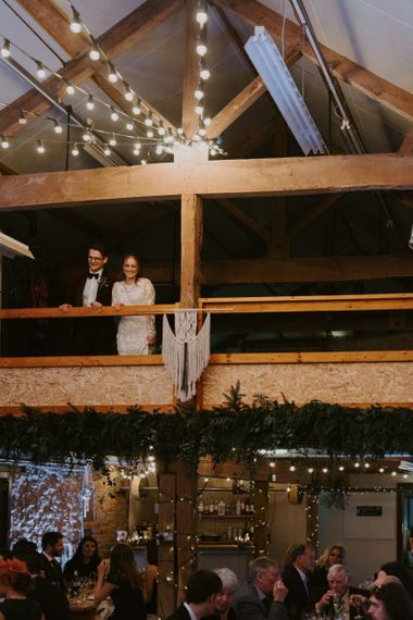 Bride and Groom Standing on the Mezzanine Looking at their Wedding Reception