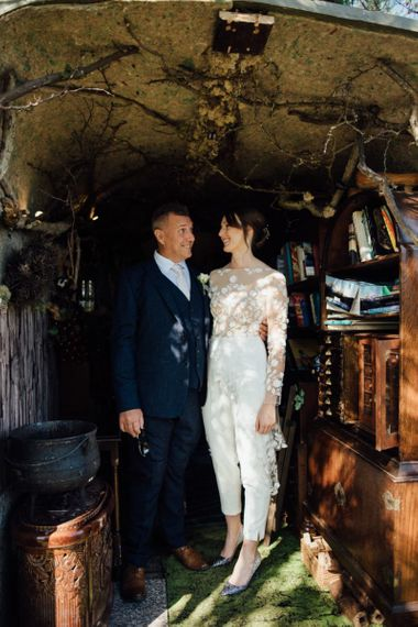 Bride wearing appliqué wedding jumpsuit at relaxed outdoor wedding in autumn