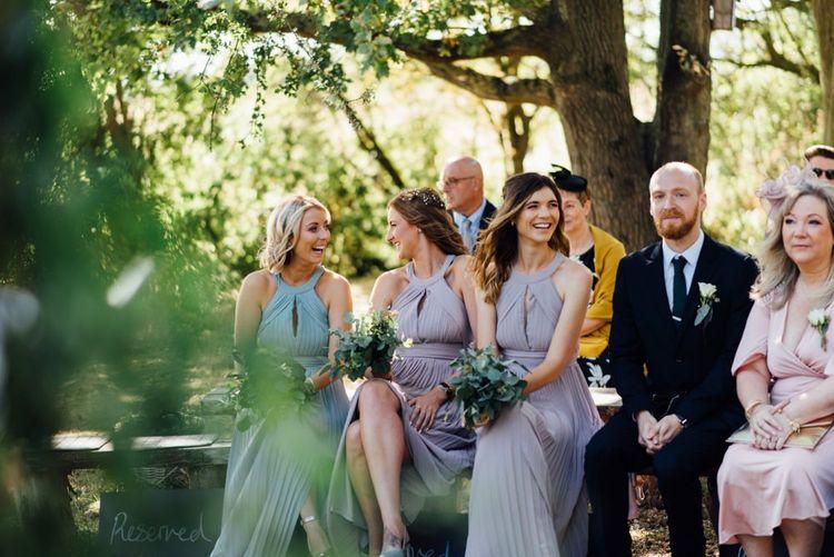 Bridesmaids in pastel halter neck dresses at outdoor woodland wedding in autumn