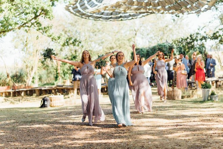 Outdoor woodland wedding celebration with pastel bridesmaid dresses