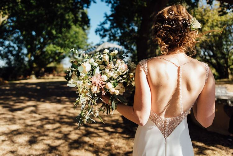 Bride wearing low back embellished dress with beautiful white and dusky pink wedding bouquet at woodland autumn wedding