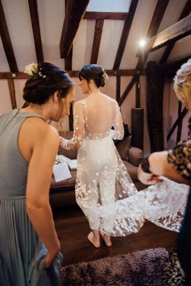Back of brides appliqué wedding jumpsuit with low back detailing at woodland wedding celebration