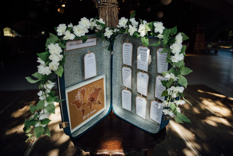 Vintage suitcase table plan at chilled woodland reception in autumn