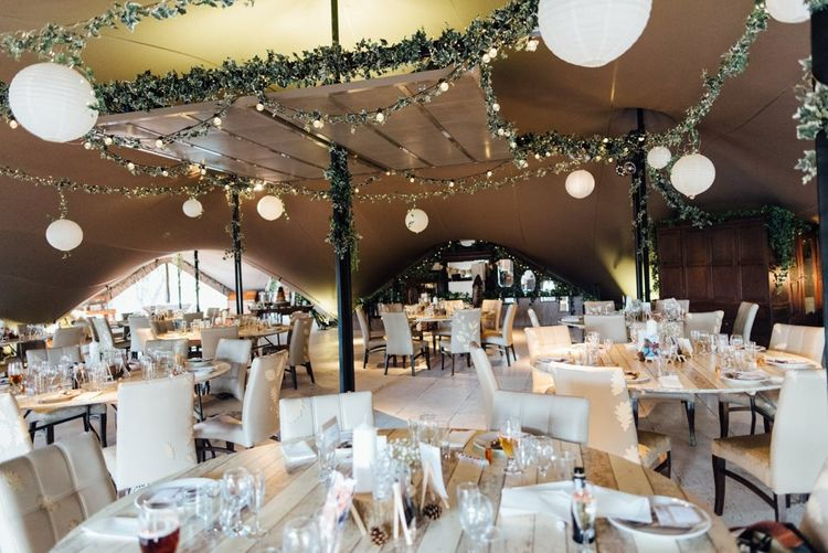 Woodland themed venue decor with fairy lights and hanging paper lanterns