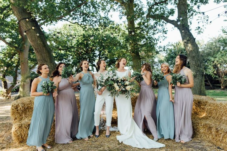 Bride in appliqué wedding jumpsuit and bride in elegant embellished gown with bridesmaids in pastel halter neck dresses at woodland celebration