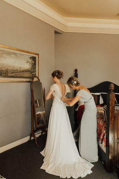 Bride with undo gets into wedding dress for Askham Hall wedding
