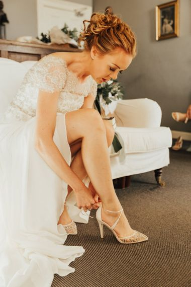Bride  with undo puts on ivory wedding shoes for Askham Hall wedding