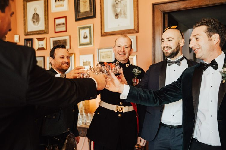 Groom and groomsmen in tuxedos toast the big day at Askham Hall wedding
