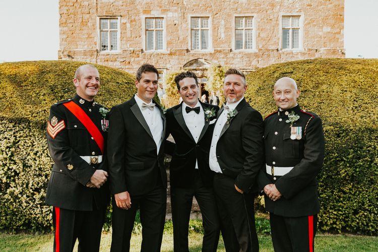 Groom with groomsmen in tuxedo and uniforms