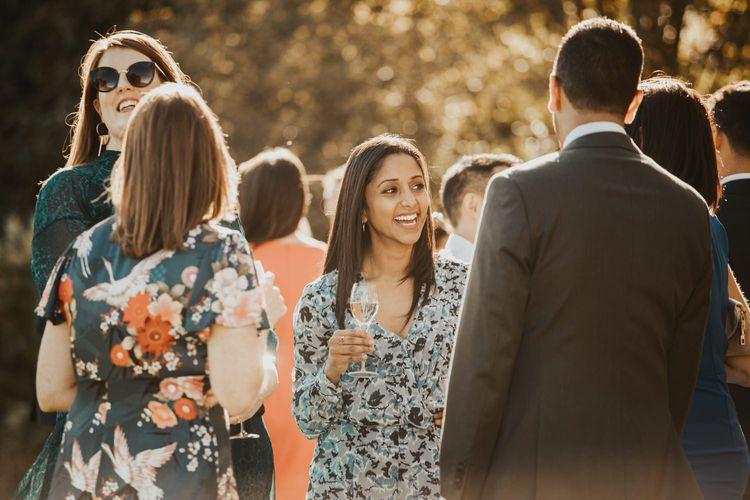 Guests enjoy drinks outside Askham Hall wedding venue