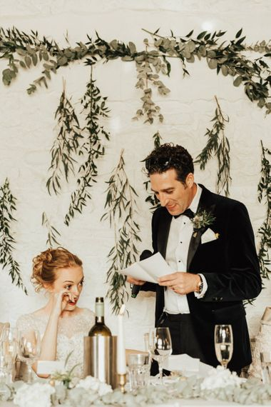 Groom wedding speech in front of hanging foliage decor