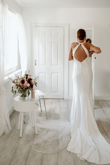 Bride on wedding morning putting on a halter neck dress