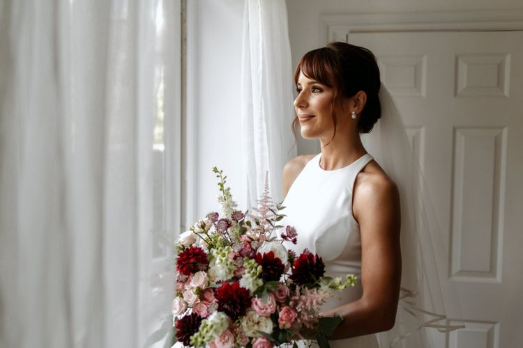Bride in minimalist wedding dress holding a pink and red bouquet