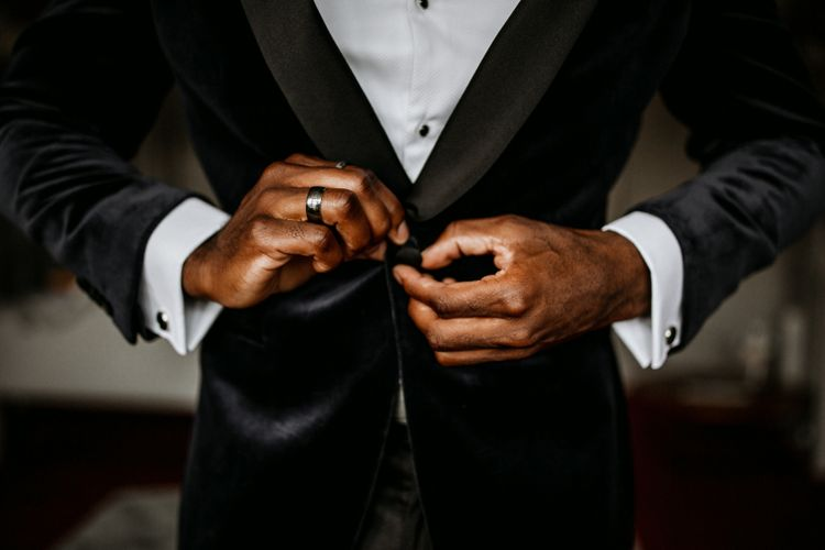 Groom tying up the buttons on his blue velvet jacket