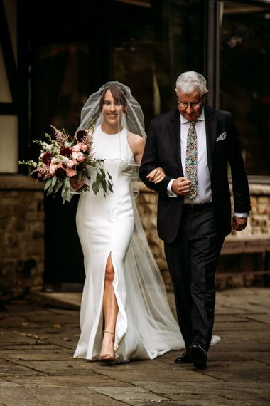 Bride walking down the aisle in fitted halter neck wedding dress