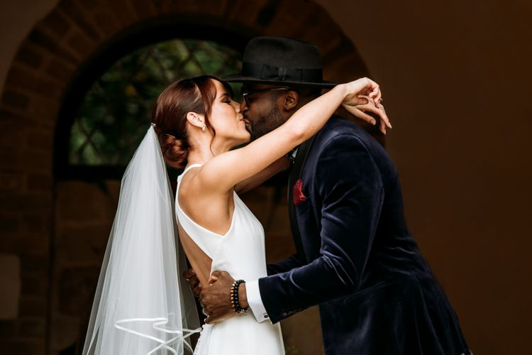 Groom in velvet dinner jacket and fedora kissing his bride at The Ravenswood wedding