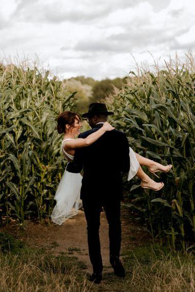 Stylish groom in velvet dinner jacket and Fedora hat picking up his bride